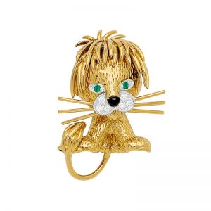 A petite 'lion ébouriffé' brooch in 18-karat gold by Van Cleef & Arpels decorated with diamonds, emeralds, and black enamel.