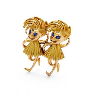 Twin dancing pixies brooch by Cartier in 18-karat gold and featuring tiny sapphire eyes.